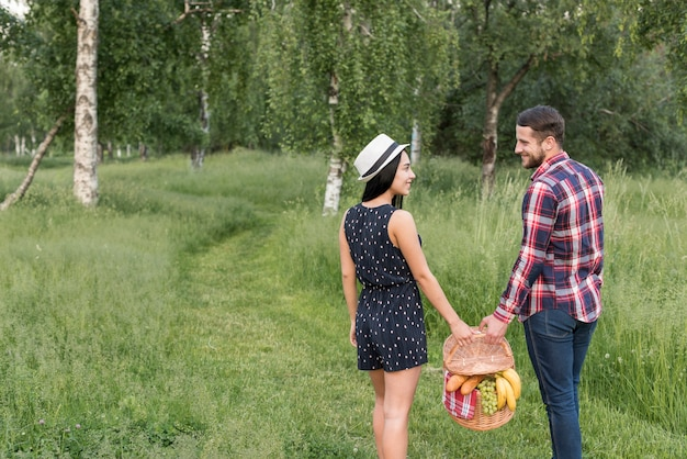 Pareja paseando mientras sostiene cesta de picnic