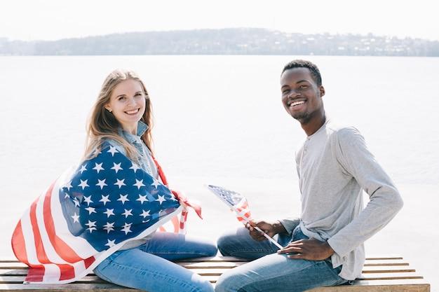 Pareja patriótica interracial sentado en el banco