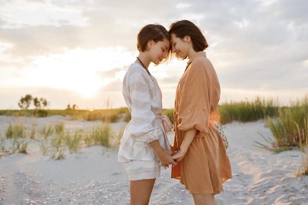 Pareja con peinado corto en ropa de verano de lino posando en la playa