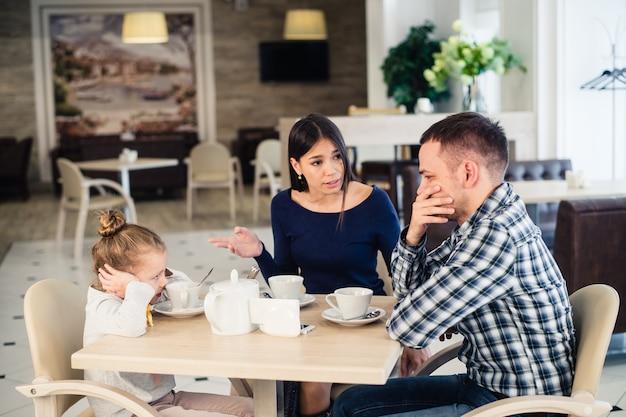 Pareja peleando delante del niño en la cafetería o restaurante