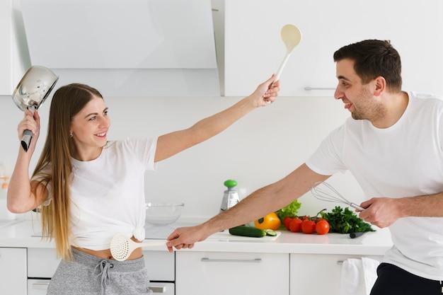 Pareja peleando con utensilios de cocina