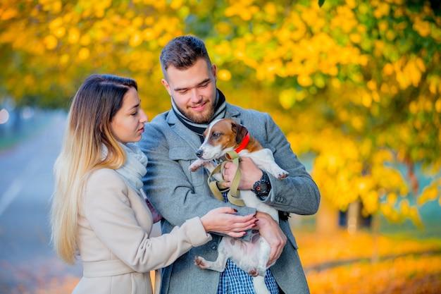 Pareja con perro en el callejón de la temporada de otoño.