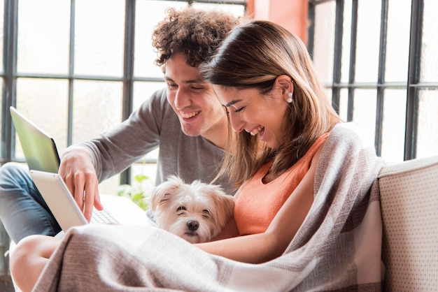 Pareja con perro trabajando en casa