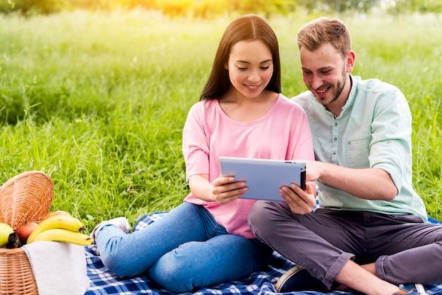 Pareja en picnic usando tableta
