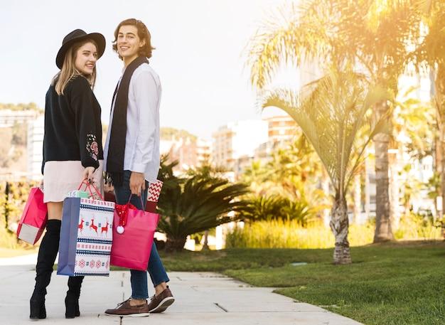 Pareja de pie con bolsas de compras de navidad en el parque