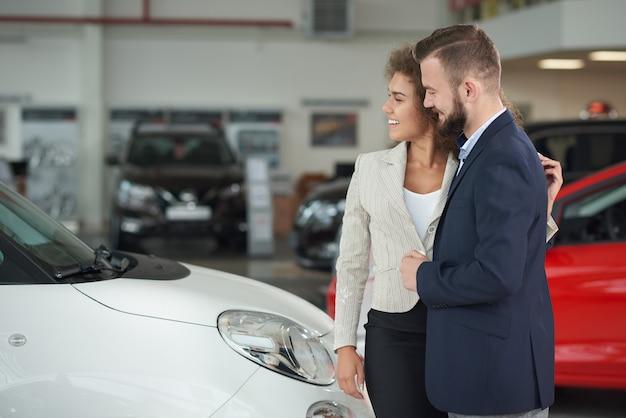 Pareja de pie en el centro del coche y elegir auto juntos.