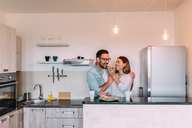 Pareja de pie en la cocina del apartamento moderno y desayunar juntos.