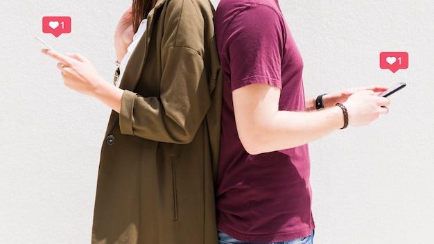Pareja de pie espalda con espalda usando el teléfono móvil con los iconos de mensajes de amor contra la pared