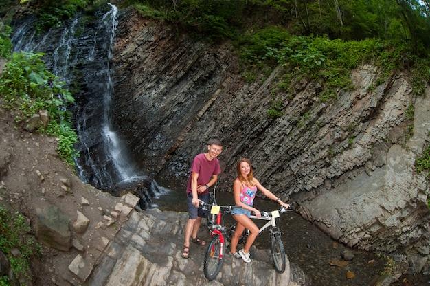 Pareja de pie junto a la cascada cerca de sus bicicletas en el bosque