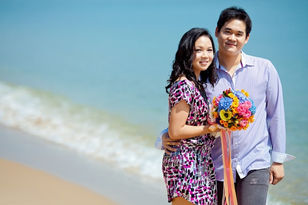Pareja de pie juntos en la playa con hermoso ramo