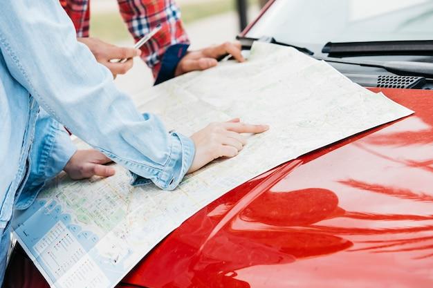 Pareja de pie con el mapa de carreteras en el coche