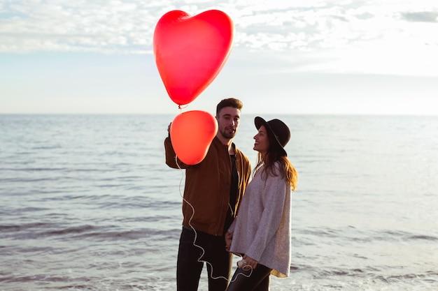 Pareja de pie en la orilla del mar con globos de corazón rojo