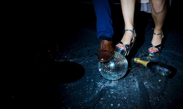 Pareja de pie en el piso con bola de discoteca