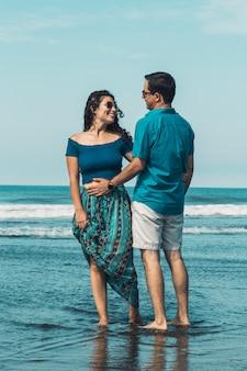 Pareja de pie en la playa en el agua de mar abrazando
