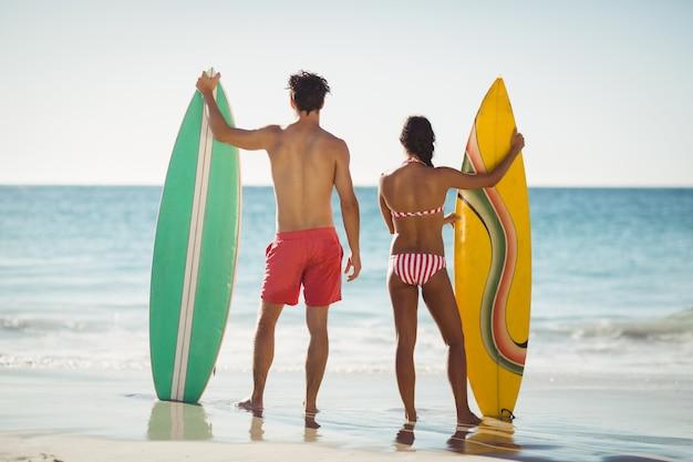 Pareja de pie con tabla de surf en la playa