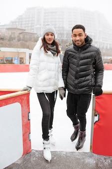 Pareja de pie y tomados de la mano en la pista de patinaje al aire libre
