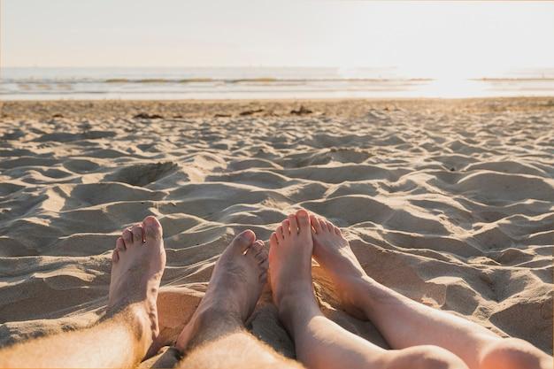 Pareja con los pies descalzos sobre la arena y el atardecer