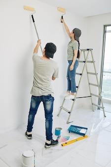 Pareja pintando paredes