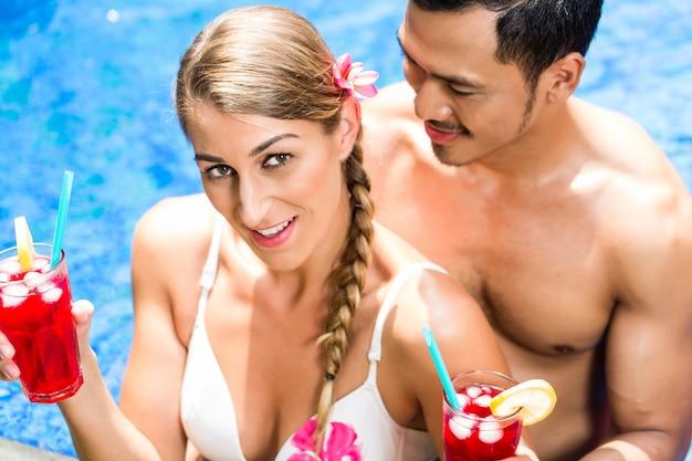Pareja en la piscina del hotel asiático bebiendo cócteles