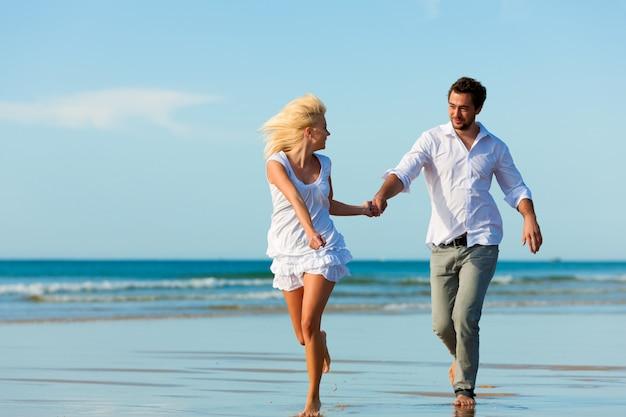 Pareja en la playa corriendo hacia un futuro glorioso