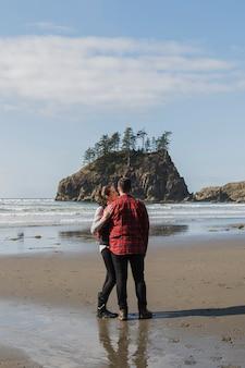 Pareja posando abrazada en la orilla