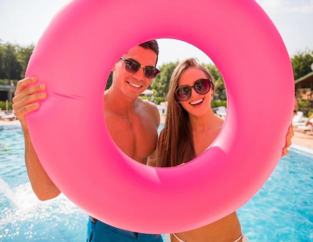 Pareja está posando con anillo de goma en la piscina.