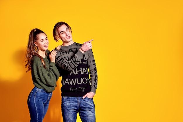 Pareja posando en jeans tipo comercial estilo de moda en la pared amarilla