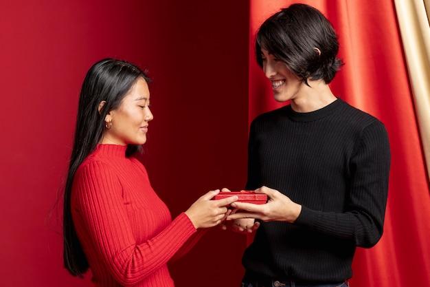 Pareja posando con regalo para año nuevo chino