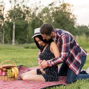 Pareja posando sobre manta de picnic