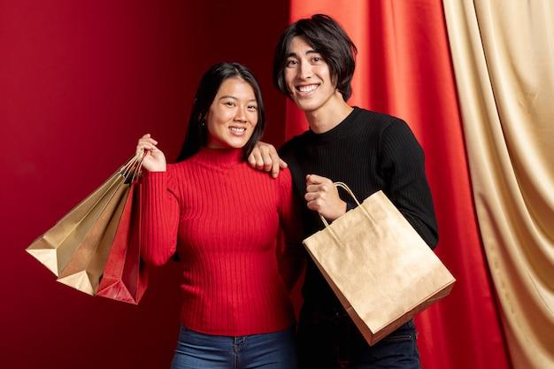 Pareja posando y sosteniendo bolsas de papel para el año nuevo chino