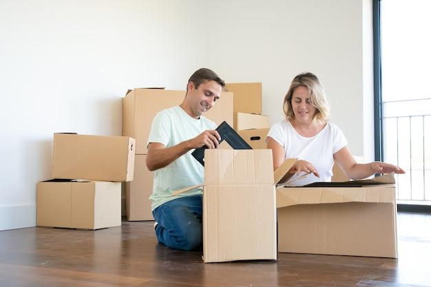 Pareja positiva desembalaje de cosas en un apartamento nuevo, sentado en el suelo y tomando objetos de cajas abiertas