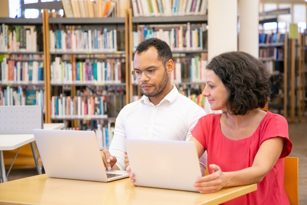 Pareja positiva de estudiantes adultos haciendo y discutiendo investigaciones