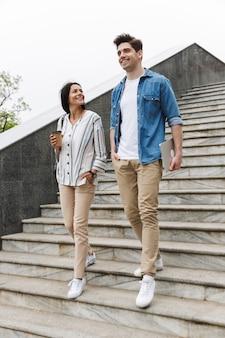 Pareja positiva, hombre y mujer, con, taza de papel, y, computadora portátil, hablar, mientras, pasear, abajo, escaleras, aire libre