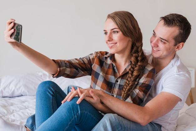 Pareja positiva joven tomando selfie en dormitorio en casa