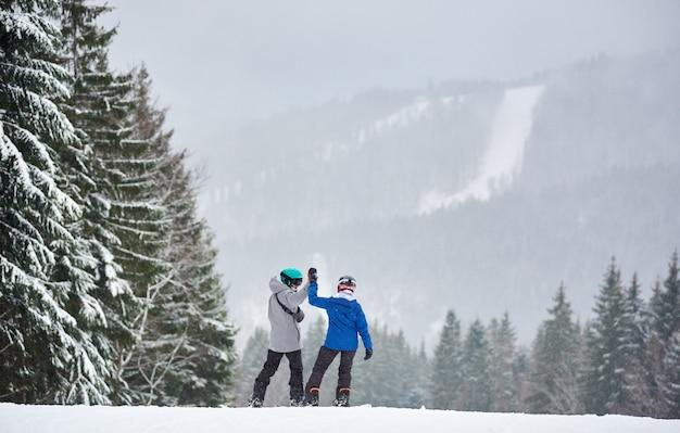 Pareja de practicantes de snowboard con las manos en alto de pie en la pendiente antes de descender a lo largo de la pendiente en tablas de snowboard. vista trasera.