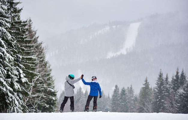 Pareja de practicantes de snowboard con las manos en alto de pie en la pendiente antes de descender por la pendiente en tablas de snowboard. vista trasera.