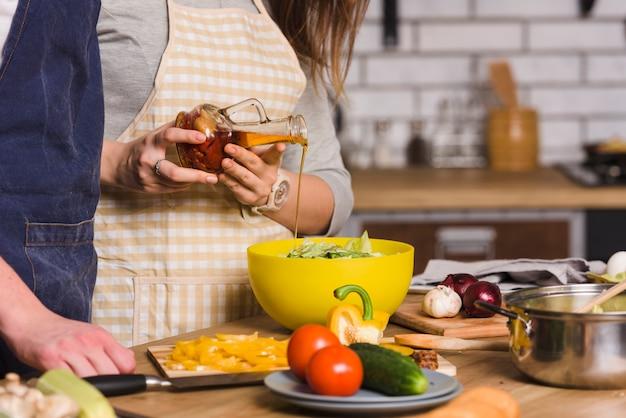 Pareja preparando ensalada de verduras en la cocina