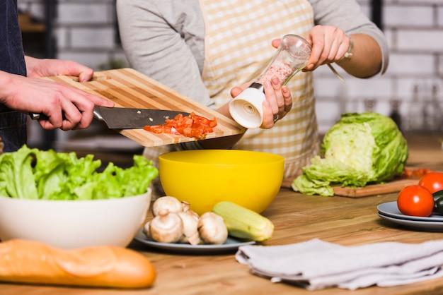 Pareja preparando ensalada de verduras