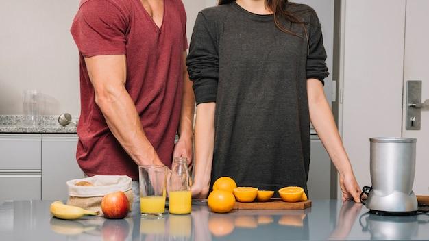 Pareja preparando naranjas para jugo