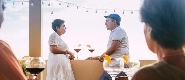 Pareja primera cita bebiendo copa de cóctel de vino tinto en la terraza del bar
