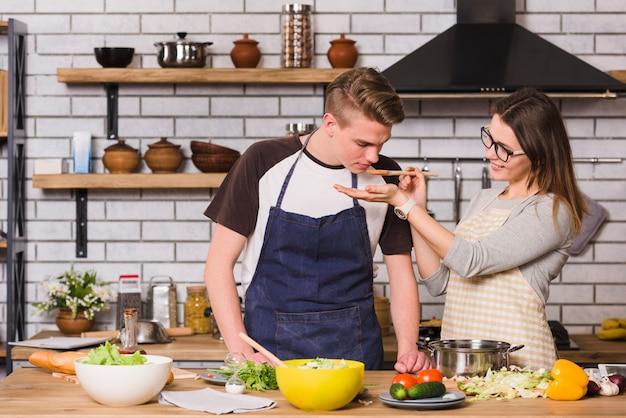 Pareja probando comida mientras cocinan juntos