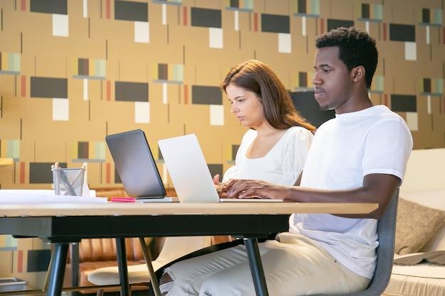 Pareja de profesionales creativos sentados juntos a la mesa con planos y trabajando en el proyecto