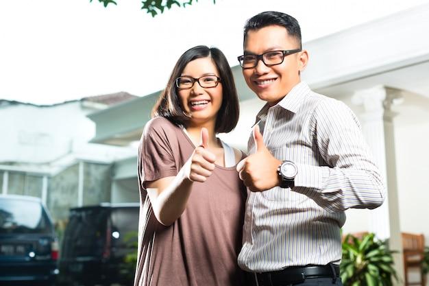Pareja de propietarios asiáticos frente a casa
