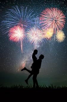 Pareja que tiene el tiempo romántico en el fondo de la noche es la vía láctea y las estrellas y fuegos artificiales
