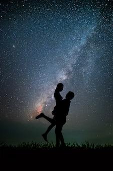 Pareja que tiene tiempo romántico en el fondo de la noche es la vía láctea y las estrellas