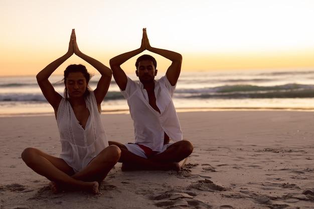 Pareja realizando yoga juntos en la playa