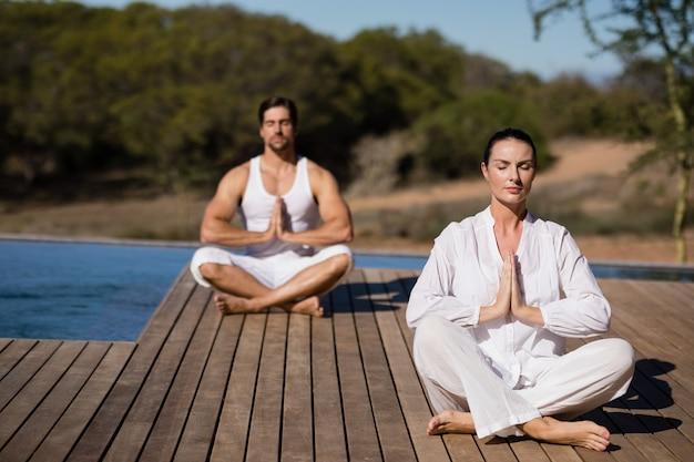 Pareja realizando yoga en vacaciones de safari