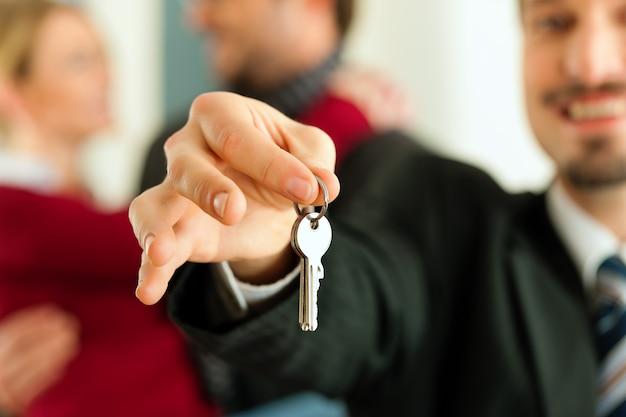Pareja recibiendo llaves de agente de bienes raíces