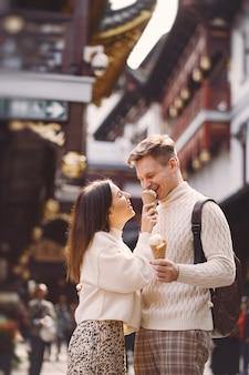 Pareja de recién casados comiendo helado de un cono en una calle de shanghai, cerca de yuyuan, china.