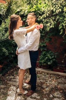 Pareja de recién casados mirándose abrazando baile y sonriendo en el día de su boda. concepto de unión y amor.
